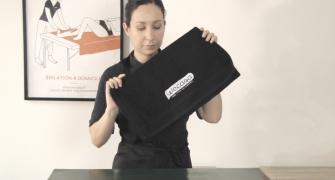 A woman folding a towel.